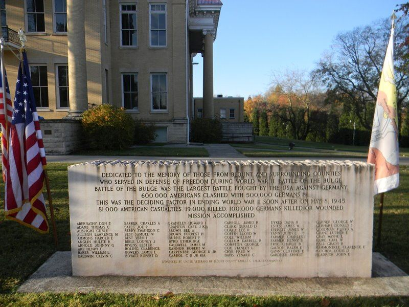 Image of the Battle of the Bulge Memorial in front of Court House, with American and Battle of the Bulge flags on either side